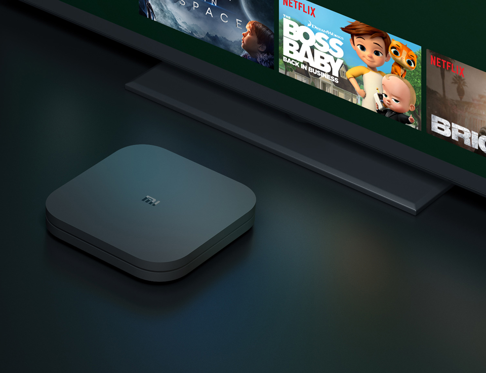 TV-Приставка Xiaomi Mi Box S International Edition возле телевизора